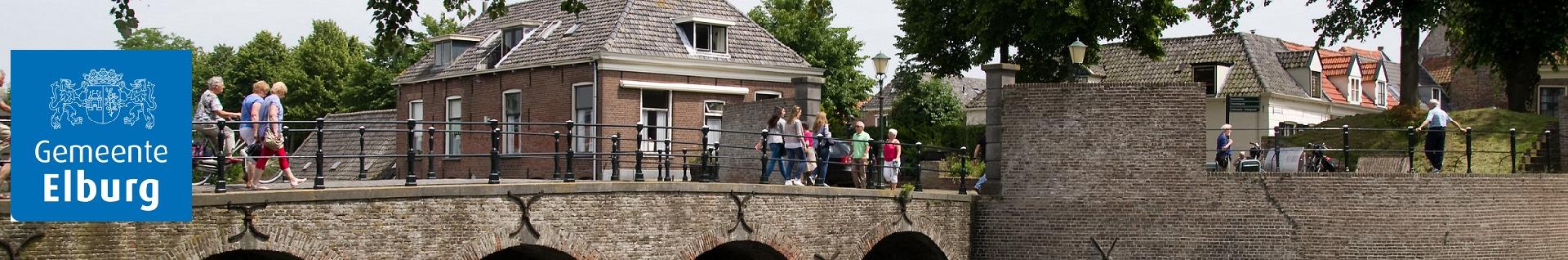 Foto van mensen die over een brug wandelen met op de achtergrond enkele huizen
